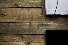 片剂和笔记本在一张老木桌上 在视图之上 图库摄影