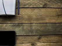 片剂和笔记本在一张老木桌上 免版税库存图片