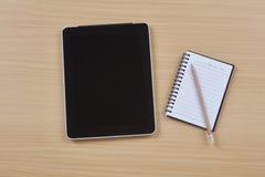 片剂和笔记本在台式 免版税库存照片