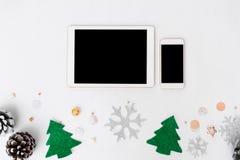 片剂圣诞节时间的智能手机构成 锥体和圣诞节装饰在白色背景 库存照片