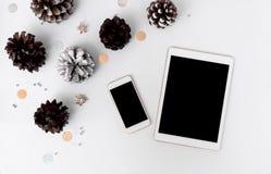 片剂圣诞节时间的智能手机构成 锥体和圣诞节装饰在白色背景 库存图片