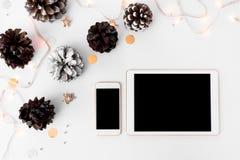 片剂圣诞节时间的智能手机构成 锥体和圣诞节装饰在白色背景 免版税库存图片