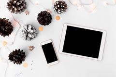 片剂圣诞节时间的智能手机构成 锥体和圣诞节装饰在白色背景 图库摄影