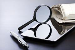 片剂放大镜笔和报纸 免版税图库摄影