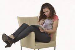 从片剂的拉丁女孩读书 库存图片