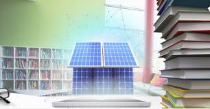片剂的电池房子在学校书桌上  皇族释放例证