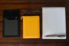 片剂计算机、笔记薄、玻璃和一支金属笔在一张黑暗的木桌上 库存照片