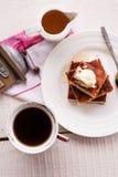 片断乳酪蛋糕和奶油,倒蜂蜜,匙子,杯子咖啡 免版税库存照片