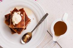 片断乳酪蛋糕和奶油,倒蜂蜜,匙子,杯子咖啡 免版税库存图片
