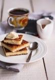 片断乳酪蛋糕和奶油,匙子,倒蜂蜜,咖啡 库存照片