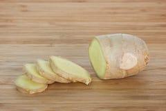 片断和切片姜在砧板根源 免版税图库摄影