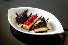 片断巧克力蛋糕和乳酪蛋糕甜点心与结冰和新鲜的草莓的 免版税库存图片