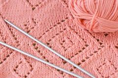 片段毯子、毛线桃红色丝球和编织针 库存图片