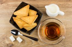 片状曲奇饼、牛奶、茶,多块的糖和匙子 免版税图库摄影