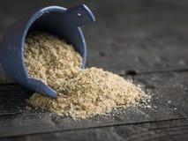 片状海盐用草本从在一张木桌上的蓝色盐瓶倾吐 库存图片