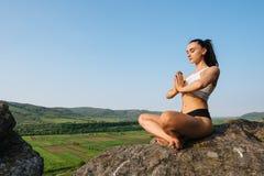 片刻的充分放松和和谐 sporrtswear实践的瑜伽的俏丽的深色的妇女在岩石 绿色山 免版税图库摄影