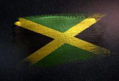 牙买加旗子由金属刷子油漆制成在难看的东西黑暗墙壁 免版税库存照片