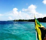 牙买加旗子落后的小船在海洋 库存照片