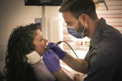 牙医与在患者的钻子一起使用 免版税库存照片