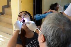 牙医从手电帮助的女性患者拔牙 库存图片