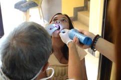 牙医从手电帮助的女性患者拔牙 免版税库存照片