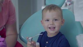 牙医准备好对检查坐在椅子的一点无忧无虑的男孩tooths在牙齿办公室 女性专家 股票录像