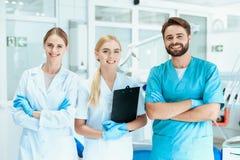 牙医和两位护士在一个牙齿办公室摆在 他们微笑着 库存图片