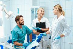 牙医和两位护士在一个牙齿办公室摆在 他们微笑着 免版税库存照片