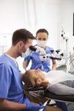牙医和他的辅助工作与牙齿显微镜 免版税库存图片