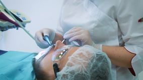 牙医在工作在办公室 一位女性医生审查一名男性患者的牙和下颌 股票视频