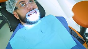 牙医在工作在办公室 一位女性医生审查一名男性患者的牙和下颌 影视素材