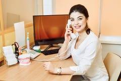 牙医女孩坐在桌上在计算机和谈话在电话 免版税库存照片