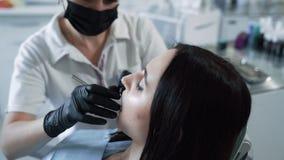 牙医审查有牙齿工具的,慢动作耐心牙 妇女在牙医办公室 股票视频