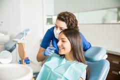 牙医对十几岁的女孩的陈列括号在诊所的镜子的 图库摄影