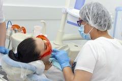 牙医对待女孩的牙 招待会的在牙医牙齿治疗,医学女孩 牙医和助理 库存图片