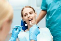 牙医弯曲了在妇女,他们对待牙 她在牙齿椅子坐 免版税库存照片