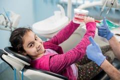 牙医椅子的愉快的女孩教育关于适当牙掠过的在牙齿诊所 牙科,口腔卫生概念 免版税库存照片