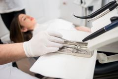 牙医用手套的手治疗患者与在牙齿诊所的牙齿工具 牙科 免版税库存图片