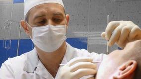 牙医非常小心地的检查和他的年轻女性患者的修理牙 库存照片