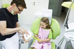 牙掠过模型的牙医椅子的女孩 库存图片