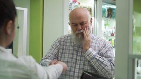 牙痛的老胡子男来药店 年轻女药师为顾客提供止痛药 影视素材