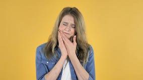 牙痛,充满牙痛的年轻俏丽的女孩在黄色背景 影视素材