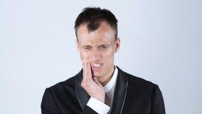 牙痛 接触他的面颊,白色背景的沮丧的年轻人 免版税库存照片