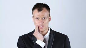 牙痛 接触他的面颊,白色背景的沮丧的年轻人 免版税库存图片