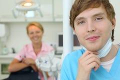 牙科医生下来在机柜屏蔽牙齿诊所 免版税图库摄影