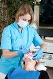 牙科医生女性她耐心的工作 免版税库存照片