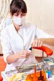 牙科医生她的办公室运作的年轻人 免版税图库摄影