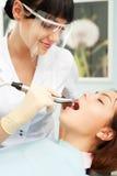牙科医生屏蔽患者面带笑容 库存图片