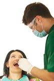 牙科医生男性耐心的妇女工作 免版税库存图片