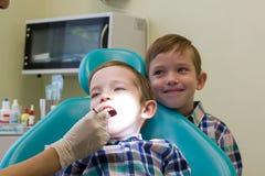牙科的招待会 一个小男孩在长沙发和他的兄弟逗留放置后边 免版税库存照片